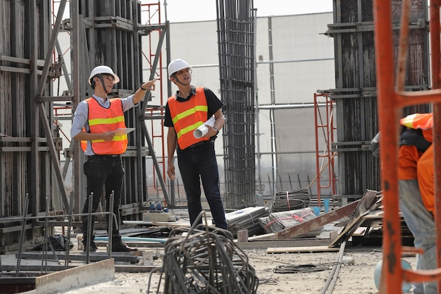 Dois engenheiros trabalham no canteiro de obras. eles estão verificando o andamento do trabalho. Foto Premium