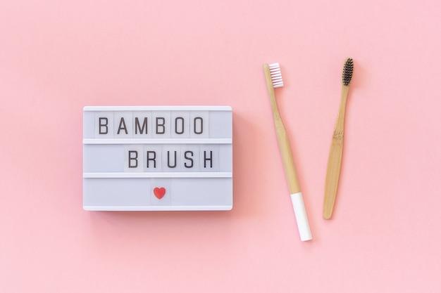 Dois escovas de bambu eco-friendly naturais e texto de mesa de bambu escova de bambu em rosa Foto Premium