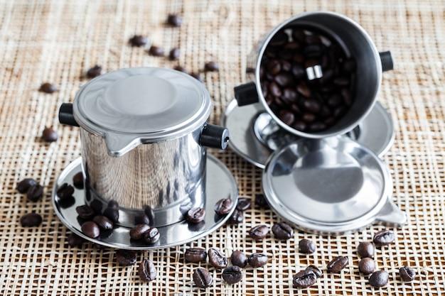 Dois fabricantes de café com os feijões de café inteiros dispersados no placemat. Foto Premium