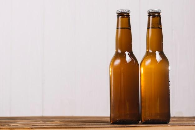 Dois, fechado, garrafas cerveja, ligado, escrivaninha madeira Foto gratuita