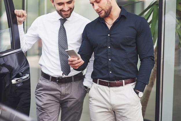 Dois felizes e confiantes jovens empresários em pé perto do escritório. Foto gratuita