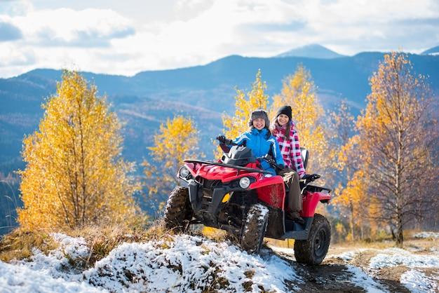 Dois, femininas, cavaleiros, atv, em, casacos, e, chapéus, ligado, um, neve coberta, rastro, em, ensolarado, dia outono, contra, árvores, com, amarela sai, e, montanhas Foto Premium