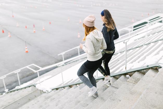 Dois feminino movimentando-se na escada no inverno Foto gratuita