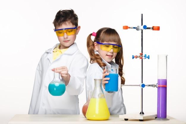 Dois filhos bonitos na aula de química, fazendo experimentos Foto gratuita