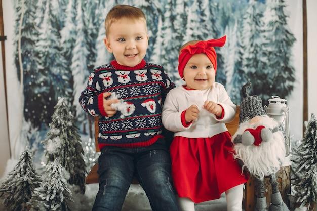 Dois filhos bonitos sentado em uma decoração de natal Foto gratuita