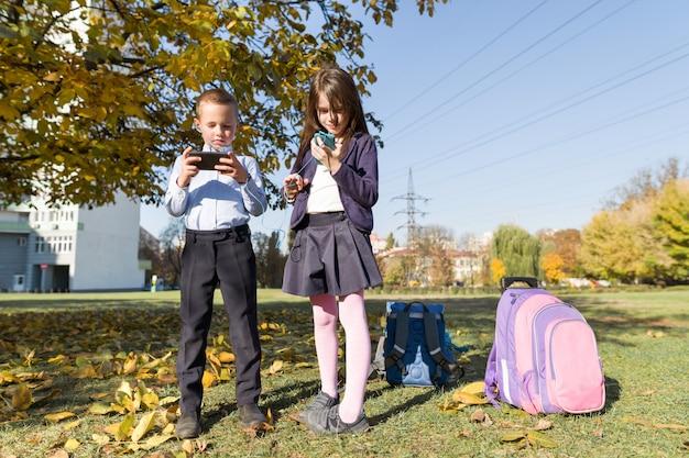 Dois filhos, com, telefones móveis Foto Premium