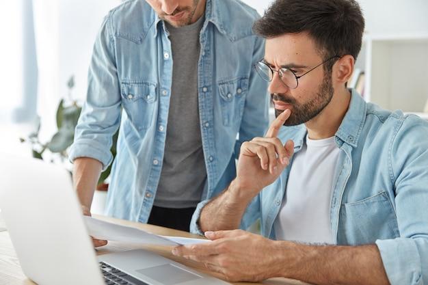 Dois financistas elegantes bem-sucedidos, analisam documentos de negócios e trabalham em um novo projeto de inicialização Foto gratuita