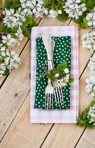 Dois garfos na superfície de madeira rústica e galhos com flores Foto Premium