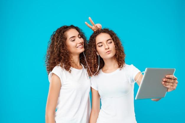 Dois gêmeos da mulher fazendo selfie sobre tablet azul. Foto gratuita