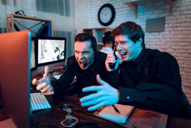 Dois guardas viram algo no monitor e gritaram. Foto Premium