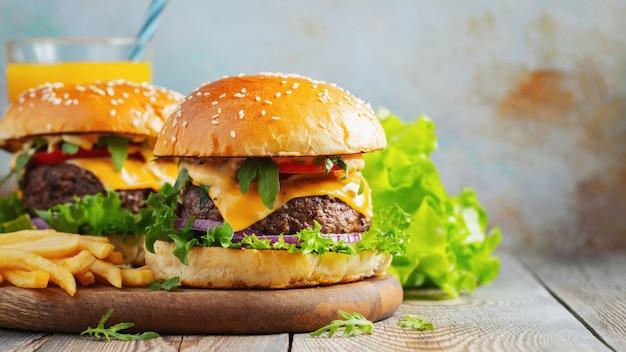 Dois hambúrgueres caseiros frescos com batatas fritas e suco de laranja Foto Premium