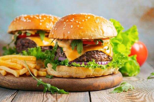 Dois hambúrgueres caseiros frescos com batatas fritas. Foto Premium