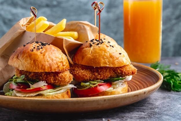 Dois hambúrgueres de mini nuggets de frango servidos com batatas fritas em caixa de papel Foto gratuita
