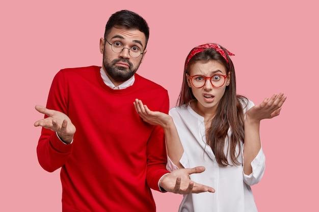 Dois hesitantes homem com a barba por fazer e uma mulher insatisfeita dão de ombros, sentem-se inseguros, têm dúvidas enquanto tomam decisões Foto gratuita