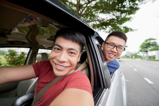 Dois homens asiáticos andando no carro na estrada e olhando para fora e motorista tomando selfie Foto gratuita