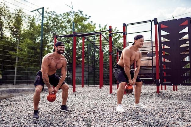Dois homens atléticos malhando com um kettlebell no quintal de ginásio de rua. Foto Premium