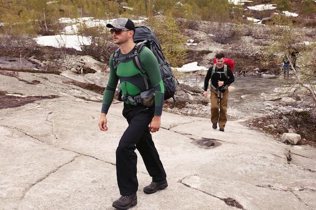 Dois homens caminham sobre as rochas nas montanhas Foto gratuita