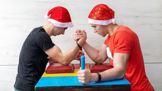 Dois homens com chapéus de natal lutando em uma queda de braço em uma academia Foto gratuita