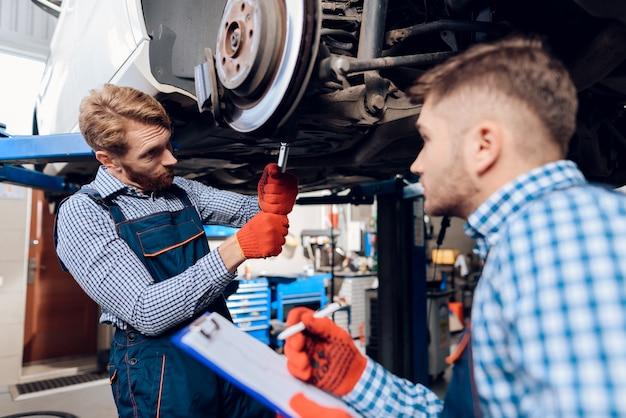 Dois homens consertando a suspensão no carro. Foto Premium