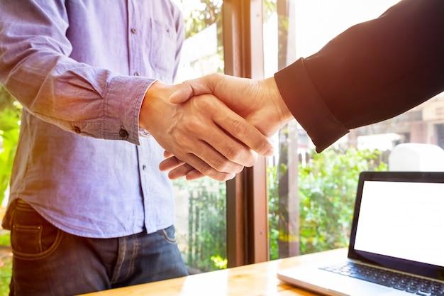Dois homens de negócios apertando as mãos Foto gratuita