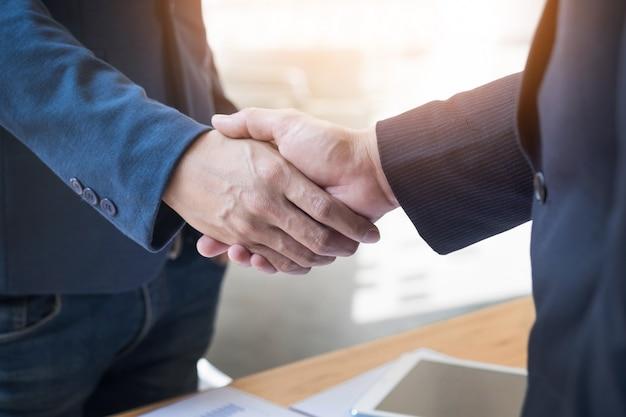 Dois homens de negócios confiantes apertando as mãos durante uma reunião no escritório, sucesso, trato, saudação e conceito de parceiro Foto gratuita