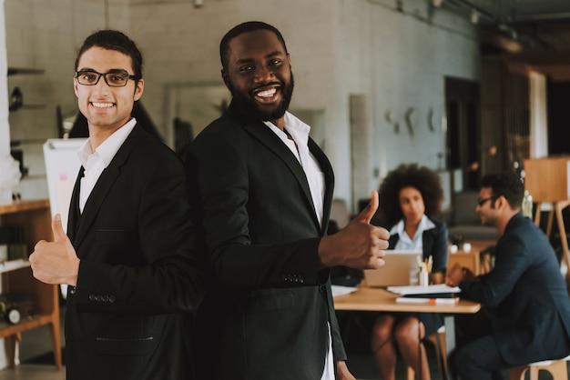 Dois homens de negócios está mostrando polegares para cima e sorrindo Foto Premium