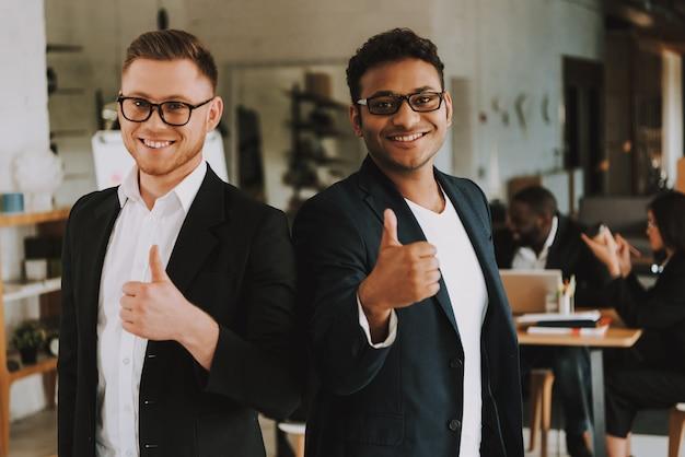 Dois homens de negócios estão mostrando os polegares acima e sorrindo. Foto Premium