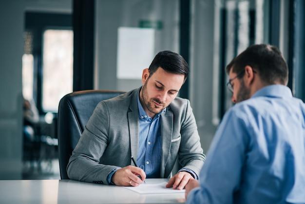 Dois homens de negócios na reunião no escritório, assinando contrato. Foto Premium