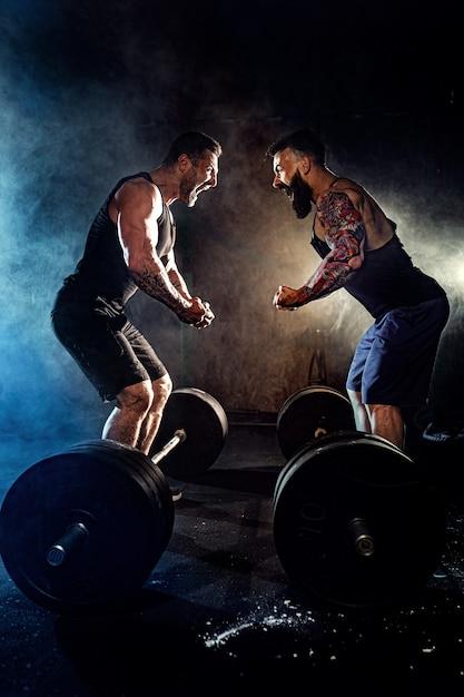 Dois homens musculosos tatuados barbudos se olham e gritam na academia Foto Premium