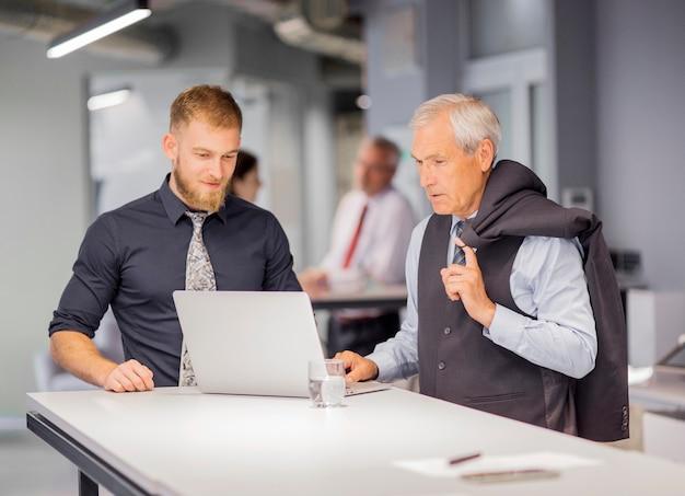 Dois, homens negócios, ficar, perto, a, tabela, olhar, laptop, em, escritório Foto gratuita
