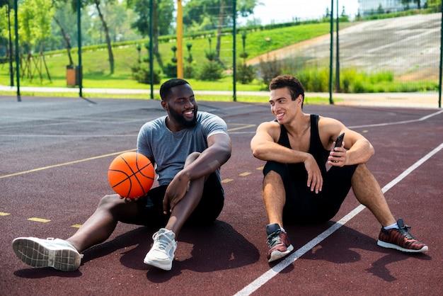 Dois homens sentados na quadra de basquete Foto gratuita