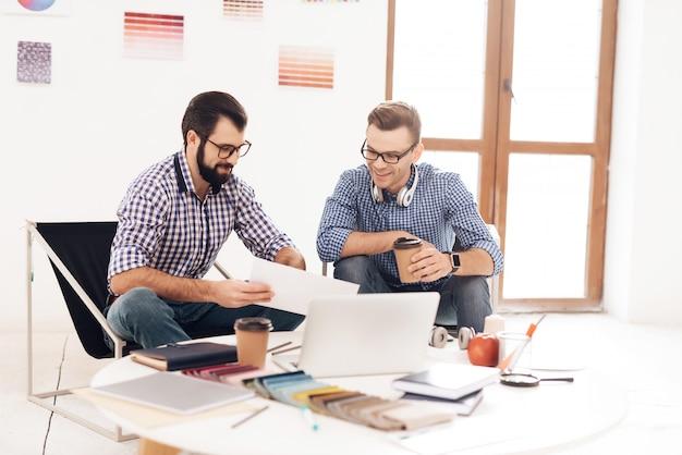 Dois homens trabalham juntos no escritório. Foto Premium