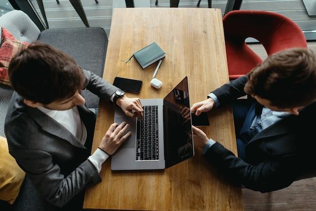 Dois homens trabalhando no laptop durante uma reunião em um café Foto gratuita