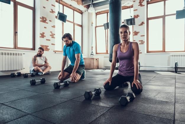 Dois indivíduos e menina descansam no assoalho do gym. intervalo. Foto Premium