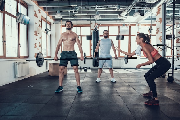 Dois indivíduos no gym lifting barbell. menina de apoio. Foto Premium