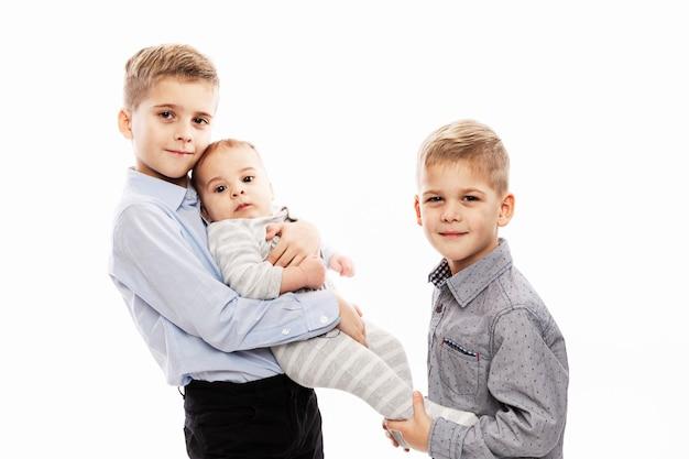 Dois irmãos estão segurando um recém-nascido. amor e ternura na família. Foto Premium