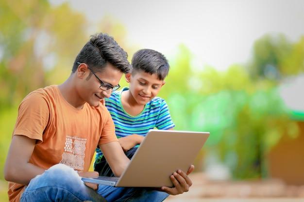 Dois irmãos indianos trabalhando no laptop Foto Premium