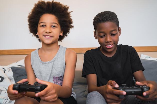 Dois irmãos jogando videogame em casa. Foto gratuita