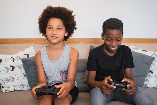 Dois irmãos jogando videogame em casa. Foto Premium