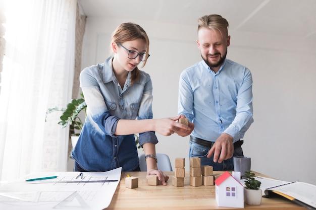 Dois, jovem, colegas, empilhando, madeira, bloco, ligado, escrivaninha negócio Foto gratuita