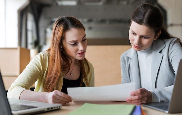 Dois, jovem, executiva, olhar, papel, em, escritório Foto gratuita