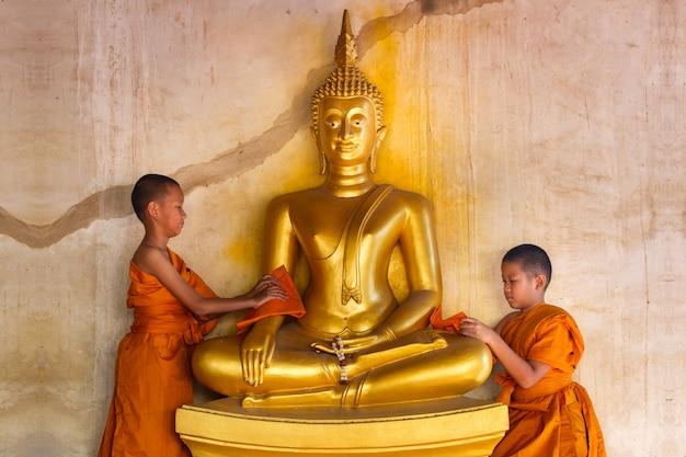 Dois, jovem, noviços, monge, esfregando, buddha, estátua, em, templo, em, tailandia Foto Premium