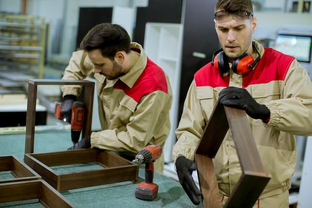Dois, jovem, trabalhadores, montagem, mobília, em, a, fábrica Foto Premium