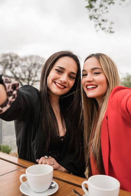 Dois jovens amigos tomando uma selfie juntos na cafeteria. Foto Premium