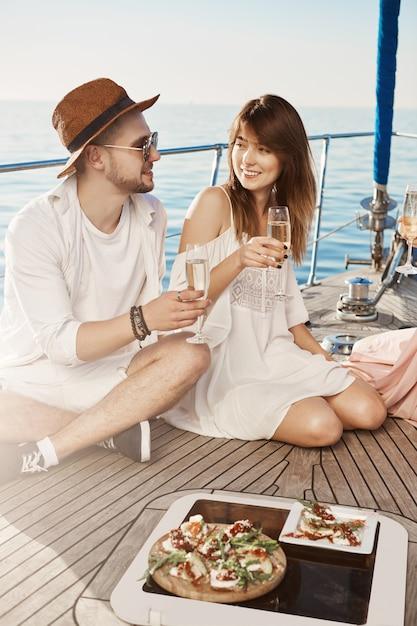 Dois jovens apaixonados almoçando e bebendo champanhe enquanto está sentado no chão do iate e discutindo algo. amigos íntimos falam sobre as datas mais terríveis que tiveram. Foto gratuita