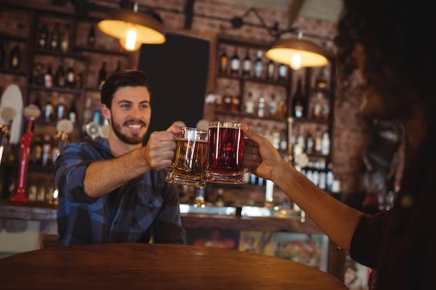 Dois jovens brindando suas canecas de cerveja Foto Premium