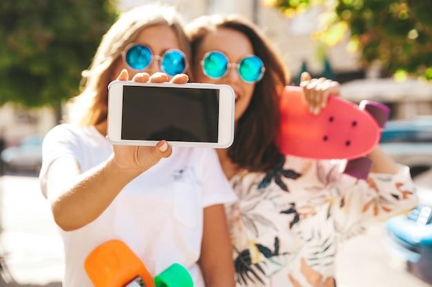 Dois jovens elegantes sorrindo morena hippie em dia ensolarado de verão em roupas hipster com posando de skate centavo Foto gratuita
