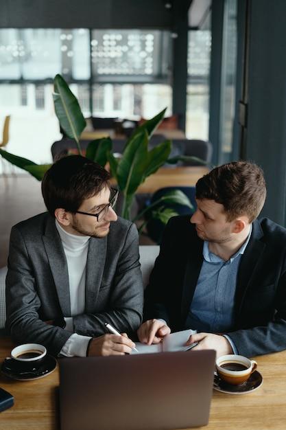 Dois jovens empresário tendo uma reunião bem sucedida no restaurante. Foto gratuita
