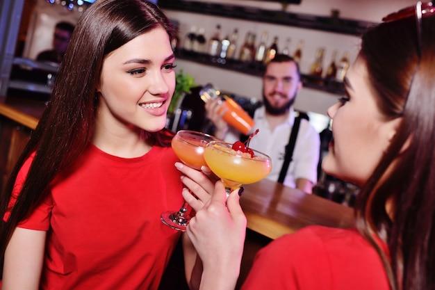 Dois jovens garotas bonitas bebem coquetéis em uma boate ou bar, divirta-se, sorria e converse com o barman Foto Premium