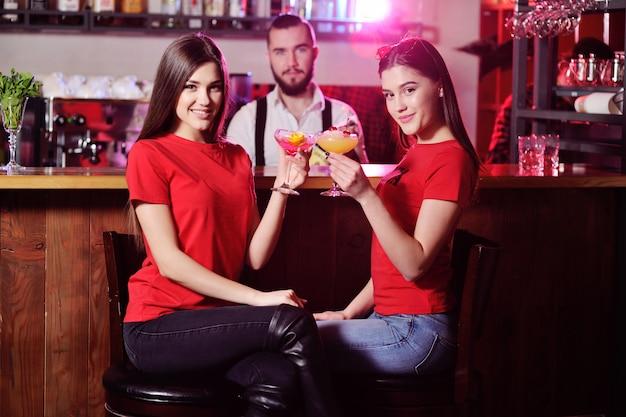 Dois jovens garotas bonitas bebem coquetéis em uma boate ou bar Foto Premium